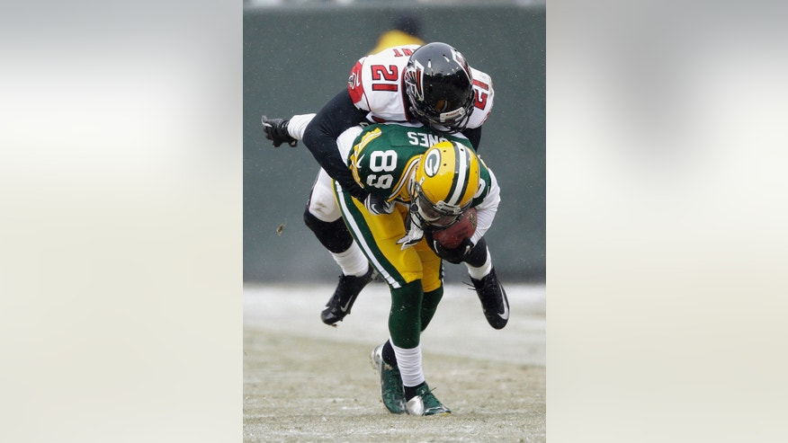 Atlanta Falcons' Desmond Trufant (21) tries to tackle Green Bay Packers' James Jones after a catch during the first half of an NFL football game Sunday, Dec. 8, 2013, in Green Bay, Wis. (AP Photo/Tom Lynn)