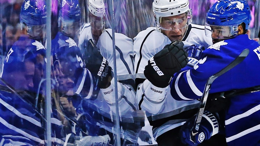 Toronto Maple Leafs' Mark Fraser, left, collides with Los Angeles Kings' Jeff Carter  againsty the glass during first period NHL hockey action in Toronto, Wednesday, Dec. 11, 2013.(AP Photo/The Canadian Press, Mark Blinch)