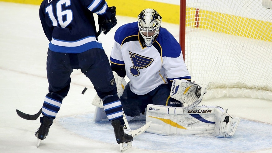Winnipeg Jets' Andrew Ladd (16) tries to screen St. Louis Blues' goaltender Brian Elliot during first period NHL hockey action in Winnipeg,  Manitoba, Tuesday, Dec. 10, 2013. (AP Photo/The Canadian Press, Trevor Hagan)