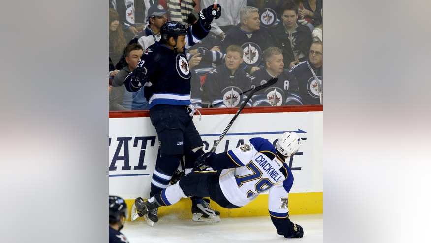 Winnipeg Jets' Dustin Byfuglien (33) hits St. Louis Blues' Adam Cracknell (79) during first period NHL hockey action in Winnipeg,  Manitoba, Tuesday, Dec. 10, 2013. (AP Photo/The Canadian Press, Trevor Hagan)