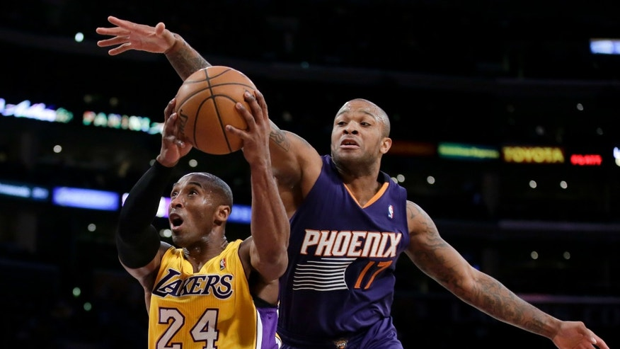 Los Angeles Lakers guard Kobe Bryant, left, drives to the basket past Phoenix Suns forward P.J. Tucker during the first half of an NBA basketball game in Los Angeles, Tuesday, Dec. 10, 2013. (AP Photo/Chris Carlson)