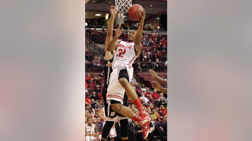 Ohio State's Lenzelle Smith, front, shoots over Bryant's Claybrin McMath during the second half of an NCAA college basketball game Wednesday, Dec. 11, 2013, in Columbus, Ohio. Ohio State beat Bryant 86-48. (AP Photo/Jay LaPrete)