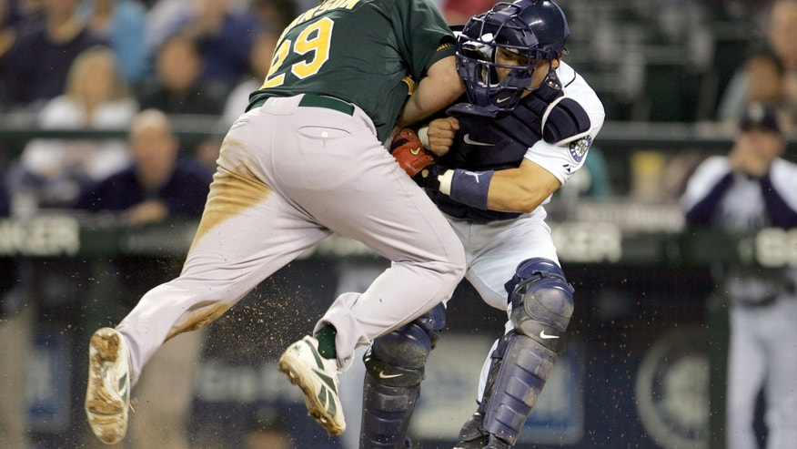 FILE - In this Sept. 27, 2006, file photo, Oakland Athletics' Dan Johnson, left, collides with Seattle Mariners' Kenji Johjima at home plate but was out on the play as Johjima held onto the ball in the ninth inning of a baseball game at Safeco Field in Seattle.  New York Mets general manager Sandy Alderson, chairman of the rules committee, announced Wednesday, Dec. 11, 2013, that Major League Baseball plans to eliminate home plate collisions. He said player health and increased awareness of concussions were behind the decision. (AP Photo/Kevin P. Casey, File)