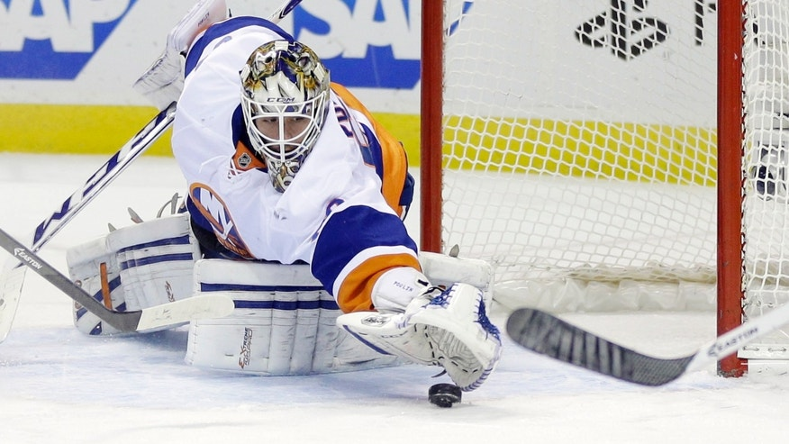 New York Islanders goalie Kevin Poulin stops a shot against the San Jose Sharks during the first period of an NHL hockey game on Tuesday, Dec. 10, 2013, in San Jose, Calif. (AP Photo/Marcio Jose Sanchez)