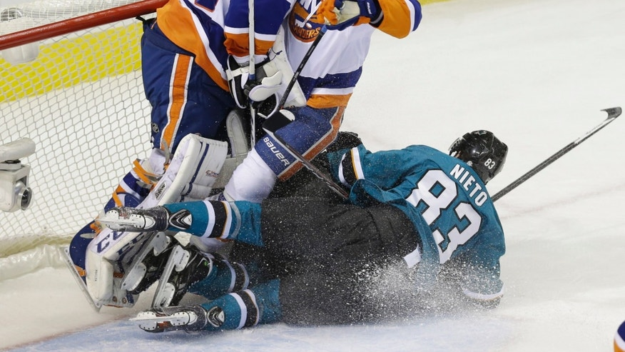San Jose Sharks' Matt Nieto (83) collides with New York Islanders' Travis Hamonic, center, and goalie Kevin Poulin during the second period of an NHL hockey game on Tuesday, Dec. 10, 2013, in San Jose, Calif. (AP Photo/Marcio Jose Sanchez)