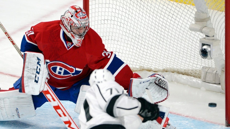 Los Angeles Kings center Jordan Nolan, front, scores against Montreal Canadiens goalie Carey Price during the first period of an NHL hockey game in Montreal on Tuesday, Dec. 10, 2013. (AP Photo/The Canadian Press, Ryan Remiorz)