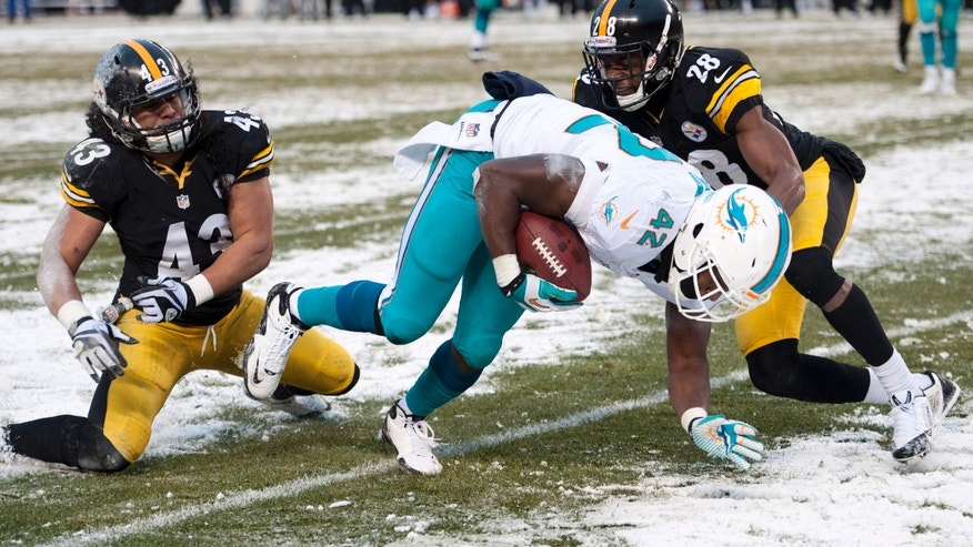 Miami Dolphins tight end Charles Clay (42) slips the tackle of Pittsburgh Steelers strong safety Troy Polamalu (43) and Pittsburgh Steelers cornerback Cortez Allen (28) and heads to the end zone for a touchdown during the second half of an NFL football game in Pittsburgh, Sunday, Dec. 8, 2013. (AP Photo/Don Wright)