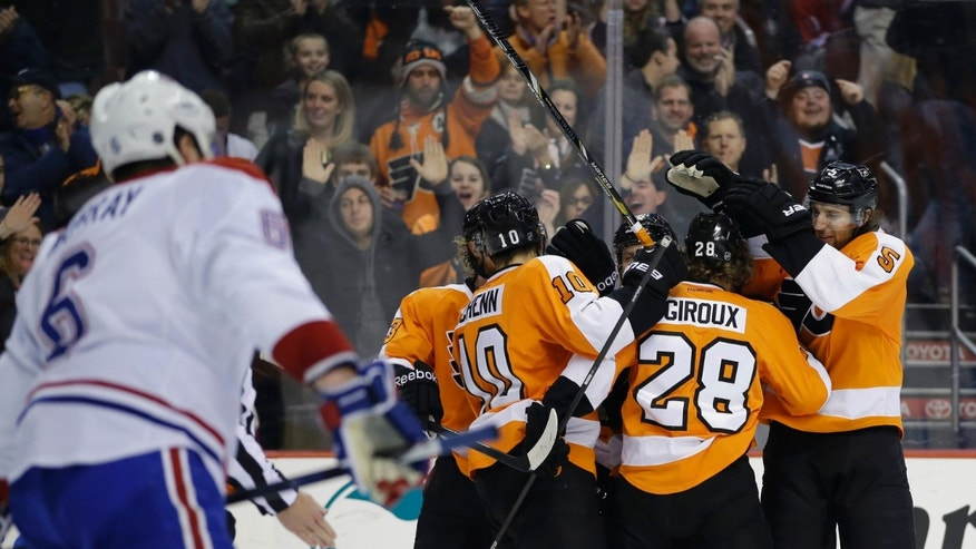 Philadelphia Flyers' Claude Giroux (28) celebrates with teammates after scoring during the second period of an NHL hockey game against the Montreal Canadiens, Thursday, Dec. 12, 2013, in Philadelphia. (AP Photo/Matt Slocum)