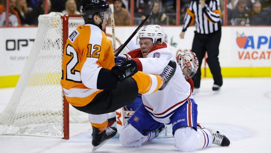 Montreal Canadiens' Brandon Prust (8) shoves Philadelphia Flyers' Michael Raffl (12), of Austria, away from the puck during the second period of an NHL hockey game, Thursday, Dec. 12, 2013, in Philadelphia. (AP Photo/Matt Slocum)