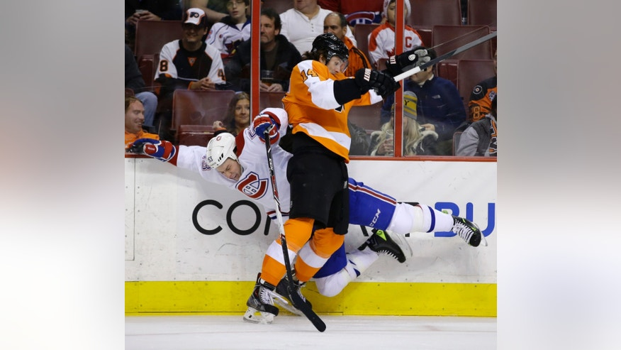 Philadelphia Flyers' Sean Couturier, right, and Montreal Canadiens' Ryan White collide during the first period of an NHL hockey game, Thursday, Dec. 12, 2013, in Philadelphia. (AP Photo/Matt Slocum)