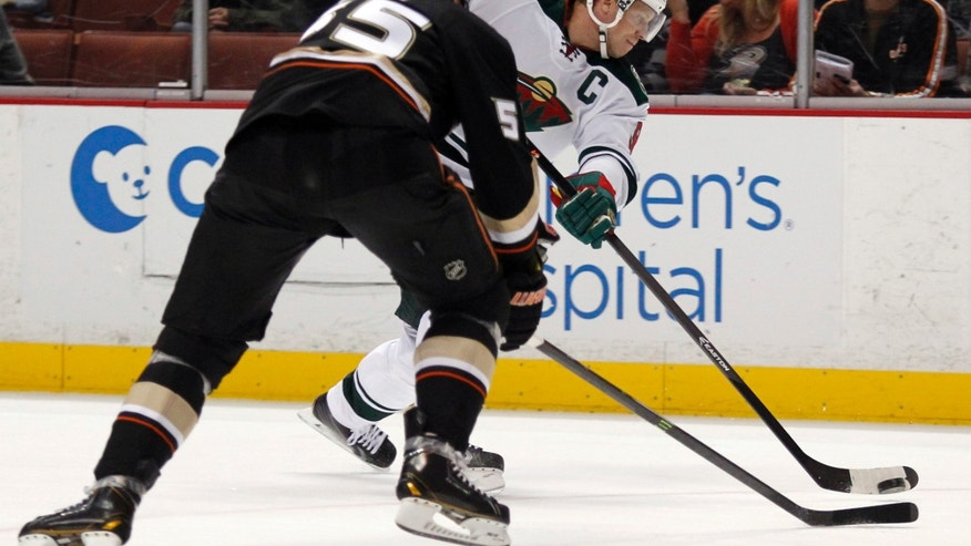 Minnesota Wild center Mikko Koivu, right, of Finland, shoots with Anaheim Ducks defenseman Bryan Allen (55) defending in the first period of an NHL hockey game on Wednesday, Dec. 11, 2013, in Anaheim, Calif. (AP Photo/Alex Gallardo)