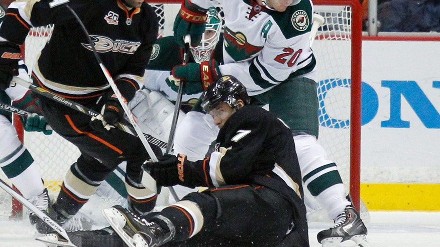 Minnesota Wild defenseman Ryan Suter (20) battles Anaheim Ducks center Andrew Cogliano, seated on ice, and right wing Daniel Winnik (34) for the puck in the first period of an NHL hockey game Wednesday, Dec. 11, 2013 in Anaheim, Calif.  (AP Photo/Alex Gallardo)
