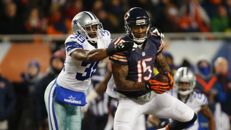 Chicago Bears wide receiver Brandon Marshall (15) makes a catch under pressure from Dallas Cowboys cornerback Brandon Carr (39) during the first half of an NFL football game, Monday, Dec. 9, 2013, in Chicago. (AP Photo/Charles Rex Arbogast)