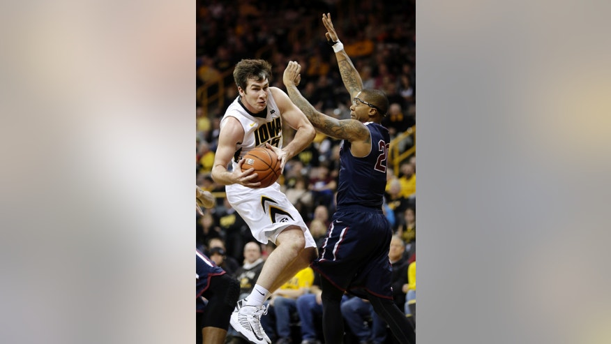 Iowa forward Zach McCabe, left, drives past Fairleigh Dickinson forward Xavier Harris during the first half of an NCAA college basketball game, Monday, Dec. 9, 2013, in Iowa City, Iowa. (AP Photo/Charlie Neibergall)