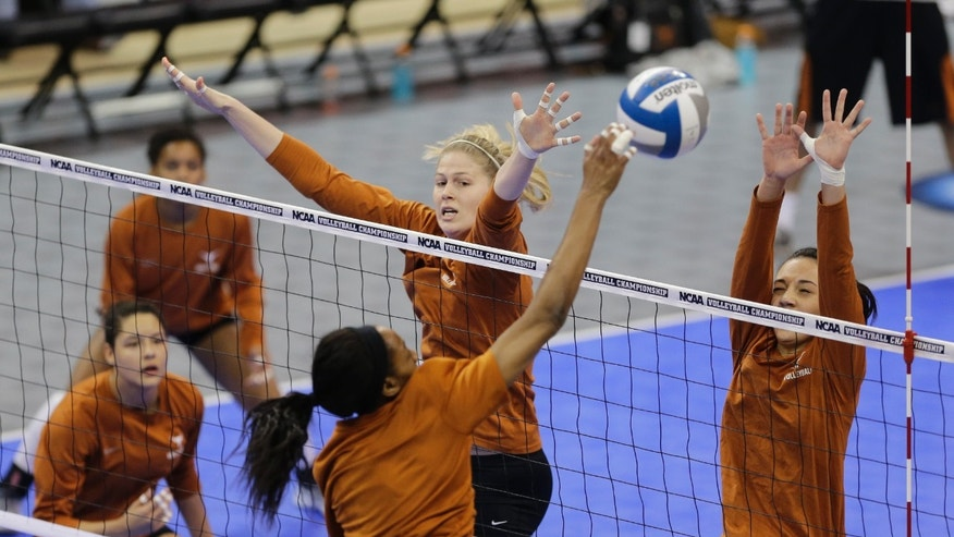Texas' Sara Hattis, top center, attempts to block Chiaka Ogbogu, bottom center, during practice in Lincoln, Neb., Thursday, Dec. 12, 2013. Texas plays American on Friday in the NCAA college volleyball Lincoln regional. (AP Photo/Nati Harnik)