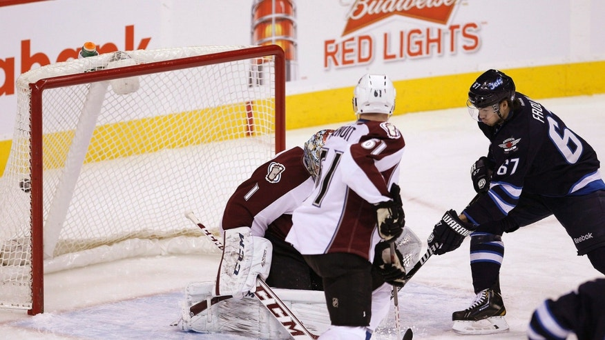 Winnipeg Jets' Michael Frolik (67) deflects Jacob Trouba's (8) shot for the goal against Colorado Avalanche's goaltender Semyon Varlamov (1) and Andre Benoit (61) during first period NHL hockey action in Winnipeg, Manitoba,  on Thursday, Dec. 12, 2013. (AP Photo/The Canadian Press, John Woods)