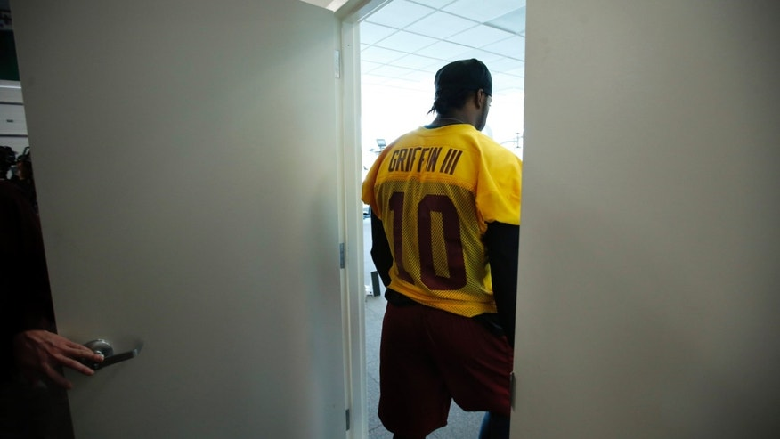 Washington Redskins quarterback Robert Griffin III, departs after speaking during a media availability at their NFL football training facility, Wednesday, Dec. 11, 2013, in Ashburn, Va. Kirk Cousins will start for the Redskins on Sunday, and Griffin III will be the No. 3 quarterback behind Rex Grossman. (AP Photo/Alex Brandon)