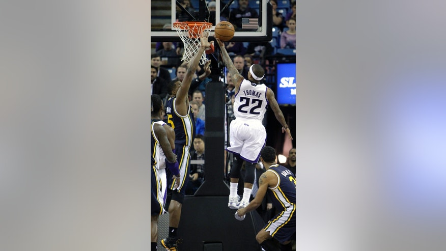 Sacramento Kings guard Isaiah Thomas, right, drives to the basket against Utah Jazz forward Derrick Favors, left, during the first quarter of an NBA basketball game in Sacramento, Calif., Wednesday, Dec. 11, 2013.(AP Photo/Rich Pedroncelli)