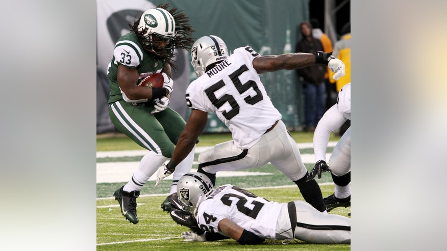 New York Jets running back Chris Ivory (33) gets by the tackle attempts of Oakland Raiders outside linebacker Sio Moore (55) and free safety Charles Woodson (24) during a touchdown run in the second half of an NFL football game, Sunday, Dec. 8, 2013, in East Rutherford, N.J. (AP Photo/Peter Morgan)