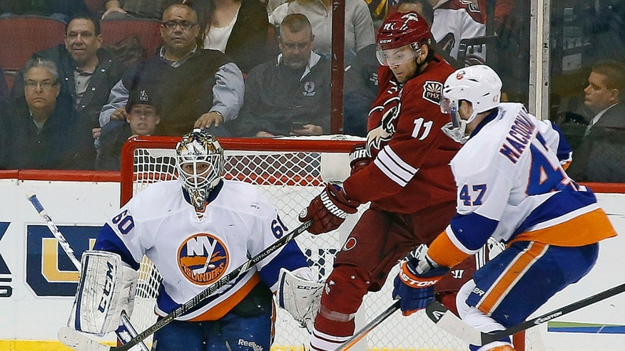 New York Islanders' Kevin Poulin (60) gives up a goal to Phoenix Coyotes' Keith Yandle as Coyotes' Martin Hanzal (11), of the Czech Republic, creates interference in front of the net while Islanders' Andrew MacDonald (47) defends during the first period of an NHL hockey game Thursday, Dec. 12, 2013, in Glendale, Ariz. (AP Photo/Ross D. Franklin)