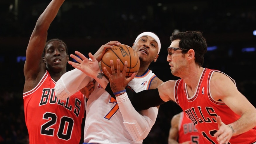 Chicago Bulls guard Kirk Hinrich (12) gets tangled up with New York Knicks forward Carmelo Anthony (7) as Chicago Bulls forward Tony Snell (20) defends in the first half of their NBA basketball game at Madison Square Garden in New York, Wednesday, Dec. 11, 2013.  (AP Photo/Kathy Willens)