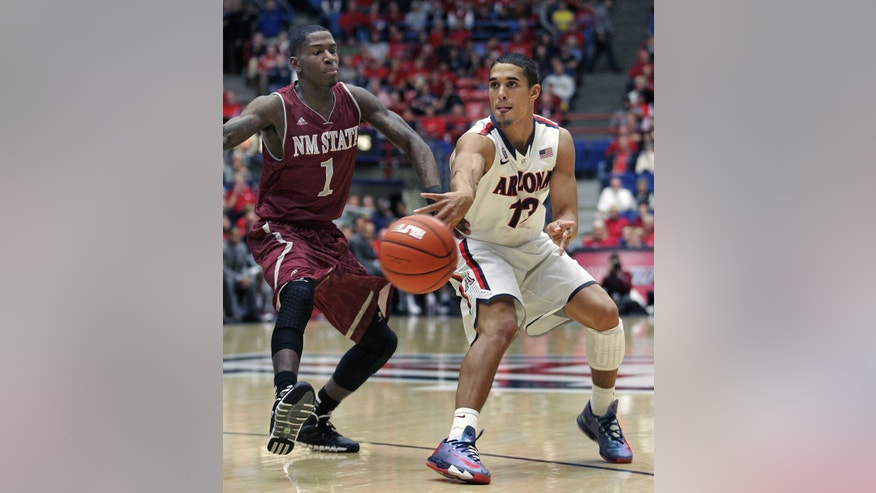 Arizona's Nick Johnson (13) passes the ball in front of New Mexico States' DK Eldridge (1) in the first half of an NCAA college basketball game on Wednesday, Dec. 11, 2013 in Tucson, Ariz.  (AP Photo/John MIller)