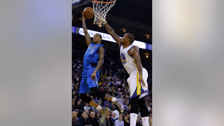 Dallas Mavericks' Monta Ellis, left, shoots over Golden State Warriors' Marreese Speights during the first half of an NBA basketball game Wednesday, Dec. 11, 2013, in Oakland, Calif. (AP Photo/Ben Margot)
