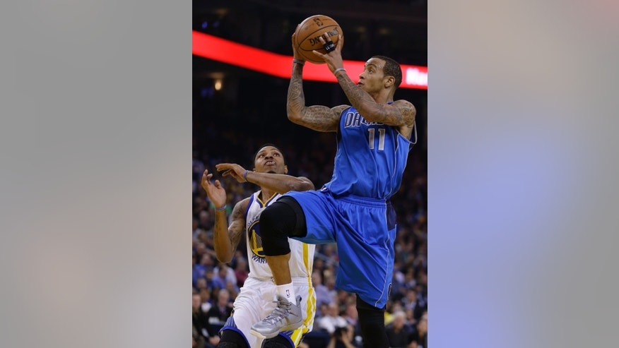 Dallas Mavericks' Monta Ellis, right, shoots over Golden State Warriors' Kent Bazemore during the first half of an NBA basketball game on Wednesday, Dec. 11, 2013, in Oakland, Calif. (AP Photo/Ben Margot)