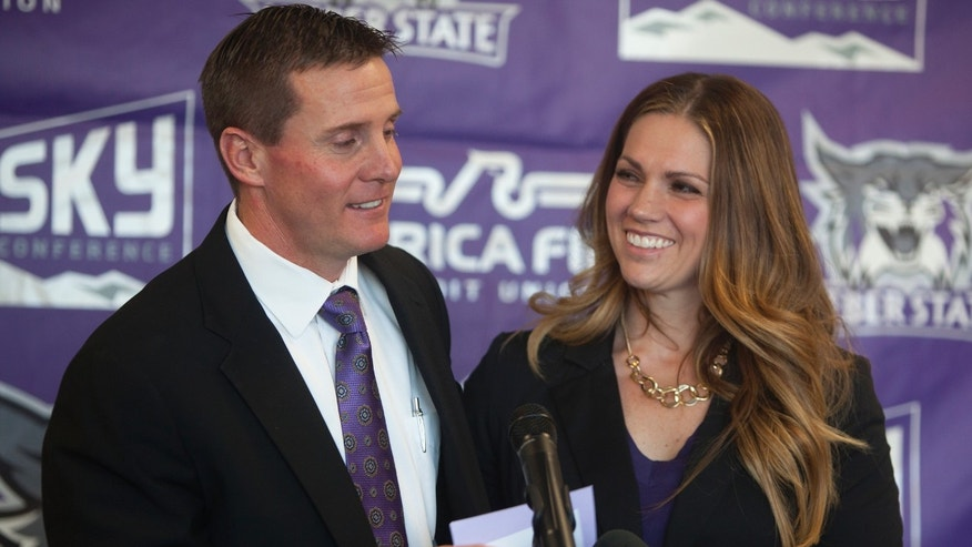 Jay Hill introduces his wife, Sara Hill, at a press conference where he was introduced as the new head NCAA college football coach at Weber State University, Thursday, Dec. 12, 2013 in Ogden, Utah. (AP Photo/Standard-Examiner, Benjamin Zack) TV OUT; MANDATORY CREDIT