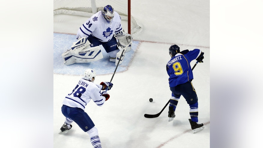 St. Louis Blues' Jaden Schwartz (9) scores past Toronto Maple Leafs goalie James Reimer and Frazer McLaren (38) during the first period of an NHL hockey game on Thursday, Dec. 12, 2013, in St. Louis. (AP Photo/Jeff Roberson)