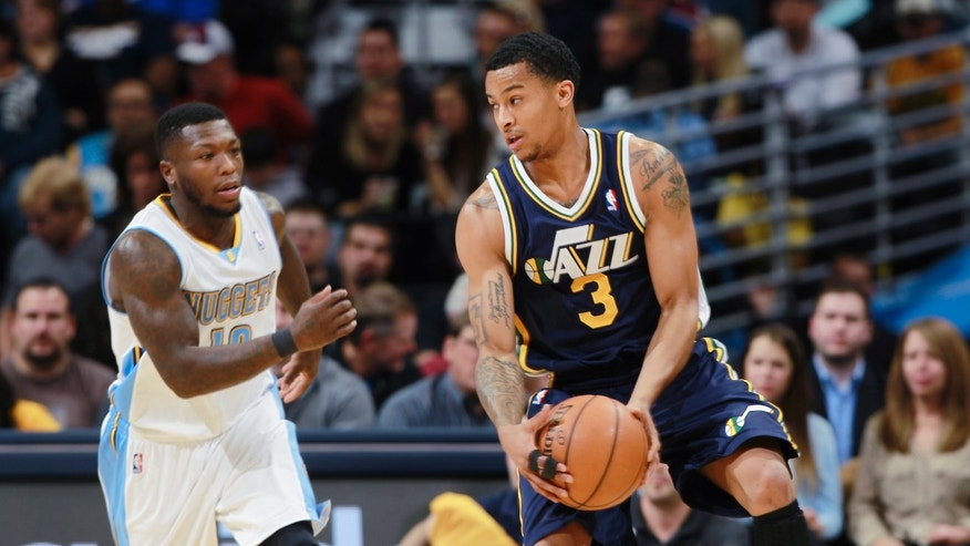 Utah Jazz guard Trey Burke, right, pulls in a loose ball as Denver Nuggets guard Nate Robinson comes in to cover in the first quarter of an NBA basketball game in Denver on Friday, Dec. 13, 2013. (AP Photo/David Zalubowski)