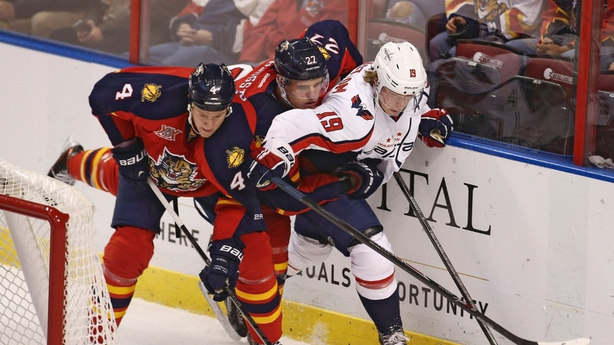 Florida Panthers players Dylan Olsen (4) and Nick Bjugstad (27) apply pressure to Washington Captials' Troy Backstrom (19) during the first period of a NHL hockey game in Sunrise, Fla., Friday, Dec. 13, 2013.  (AP Photo/J Pat Carter)