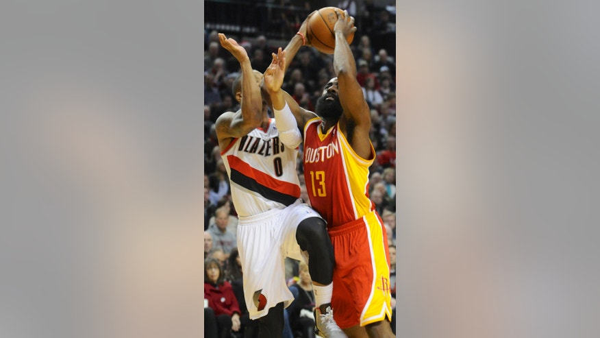 Houston Rockets' James Harden (13) shoots against Portland Trail Blazers'  Damian Lillard (0) during the first half of an NBA basketball game in Portland, Ore.,Thursday Dec. 12, 2013. (AP Photo/Greg Wahl-Stephens)