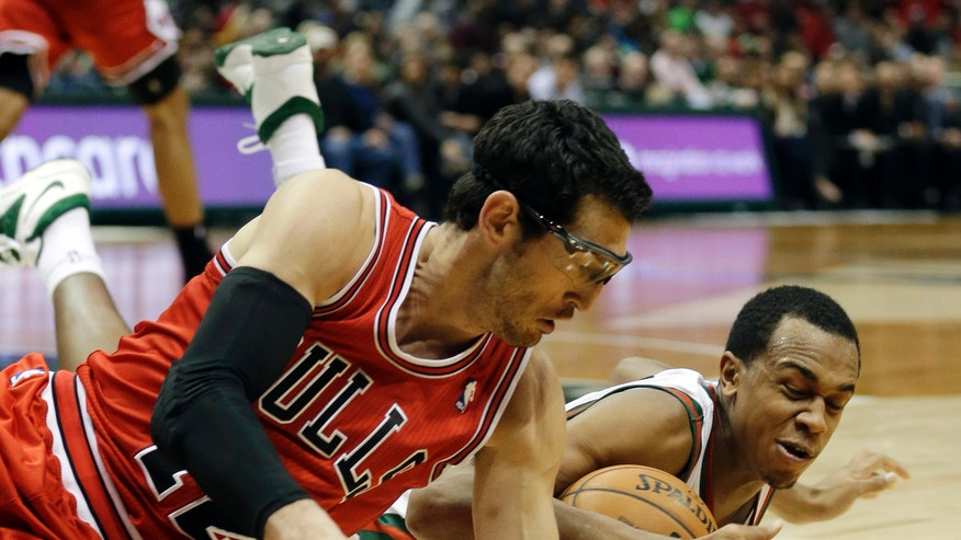 Chicago Bulls' Kirk Hinrich, left, and Milwaukee Bucks' John Henson go after a loose ball during the second half of an NBA basketball game Friday, Dec. 13, 2013, in Milwaukee. (AP Photo/Morry Gash)