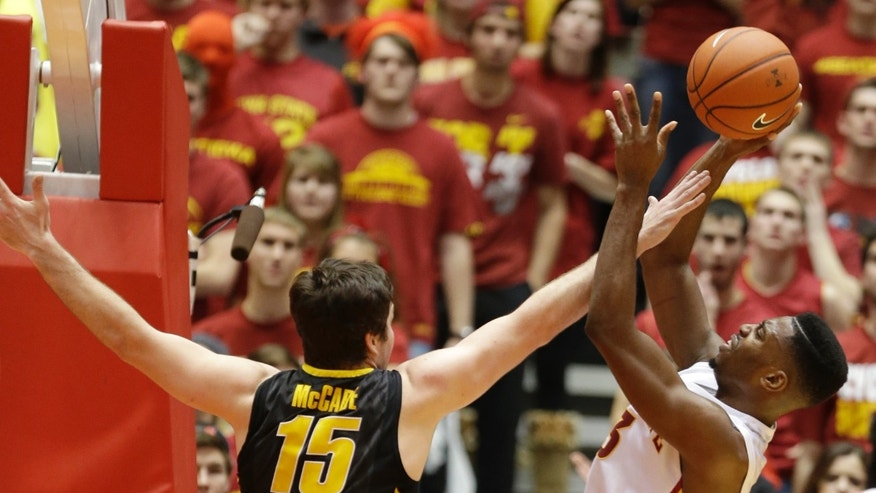 Iowa State forward Melvin Ejim, right, shoots over Iowa forward Zach McCabe during the first half of an NCAA college basketball game on Friday, Dec. 13, 2013, in Ames, Iowa. (AP Photo/Charlie Neibergall)