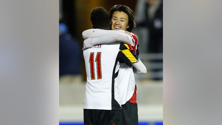 Maryland's Mikias Eticha (11) and Tsubasa Endoh embrace after they defeated Virginia 2-1 during a semifinal match in the NCAA Division 1 men's soccer championships in Chester, Pa., Friday, Dec. 13, 2013. Maryland moves on to play Notre Dame for the championship on Sunday. (AP Photo/Rich Schultz)