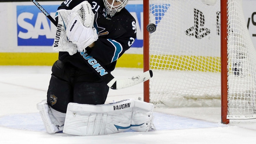 San Jose Sharks goalie Antti Niemi (31), of Finland, deflects a shot on goal against the Minnesota Wild during the second period of an NHL hockey game on Thursday, Dec. 12, 2013, in San Jose, Calif. (AP Photo/Marcio Jose Sanchez)