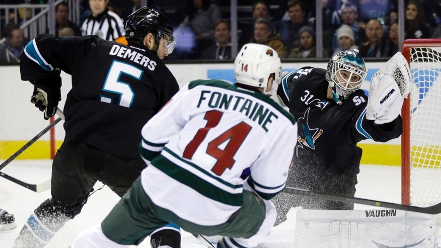 San Jose Sharks goalie Antti Niemi (31), of Finland, stops a shot next to Minnesota Wild's Justin Fontaine (14) and teammate Jason Demers (5) during the second period of an NHL hockey game on Thursday, Dec. 12, 2013, in San Jose, Calif. (AP Photo/Marcio Jose Sanchez)