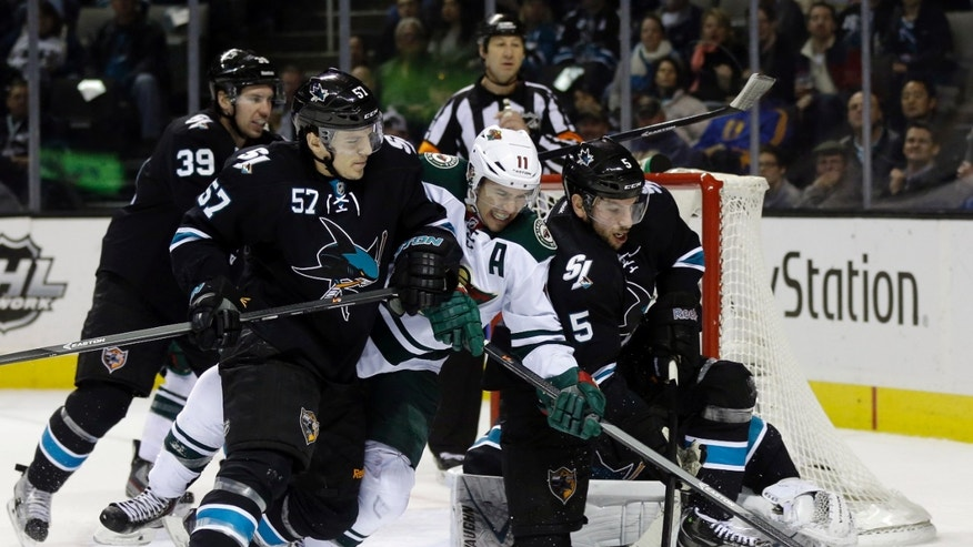 Minnesota Wild's Zach Parise (11) gets tangled with San Jose Sharks' Tommy Wingels (57) and Jason Demers (5) during the second period of an NHL hockey game on Thursday, Dec. 12, 2013, in San Jose, Calif. (AP Photo/Marcio Jose Sanchez)