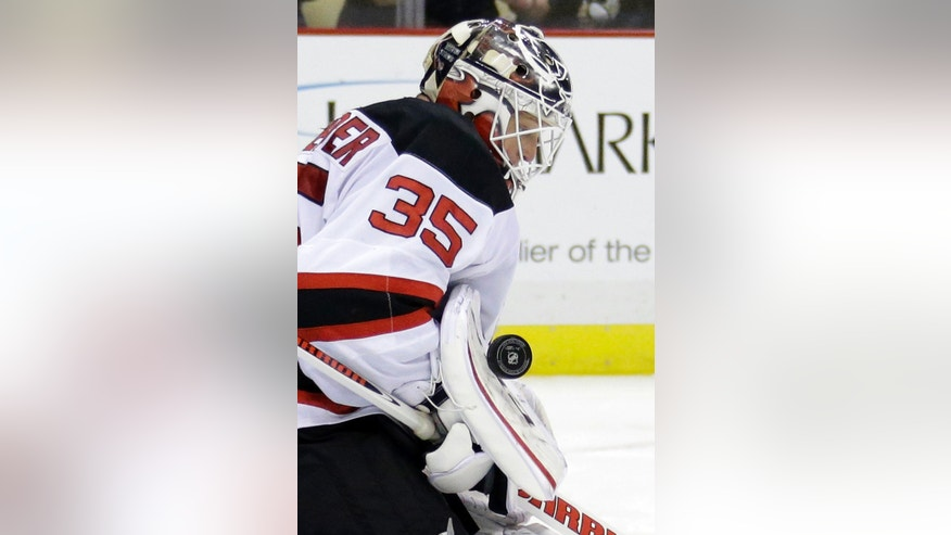 New Jersey Devils goalie Cory Schneider stops a shot in the second period of an NHL hockey game against the Pittsburgh Penguins in Pittsburgh, Friday, Dec. 13, 2013. (AP Photo/Gene J. Puskar)