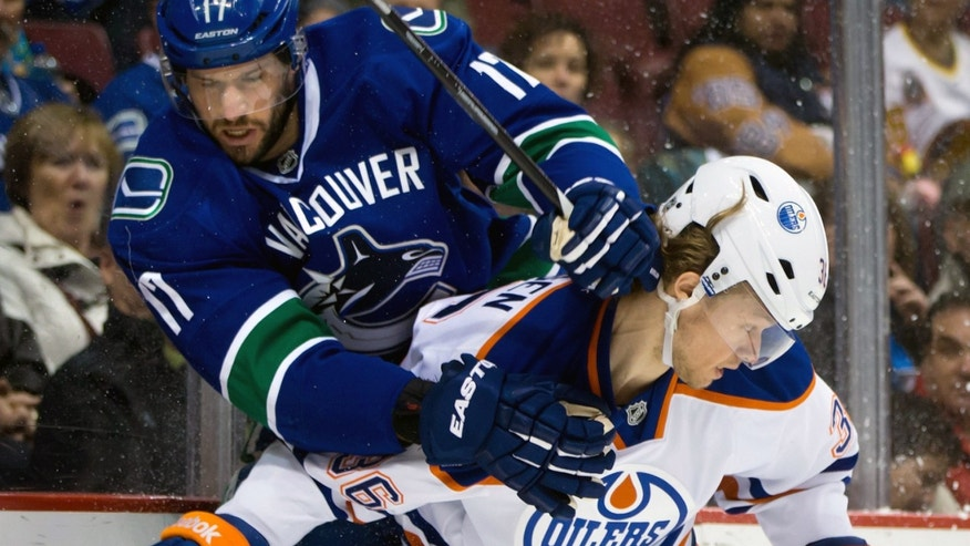 Vancouver Canucks' Ryan Kesler, left, and Edmonton Oilers' Philip Larsen, of Denmark, collide during first-period NHL hockey game action in Vancouver, British Columbia, Friday, Dec. 13, 2013. (AP Photo/The Canadian Press, Darryl Dyck)