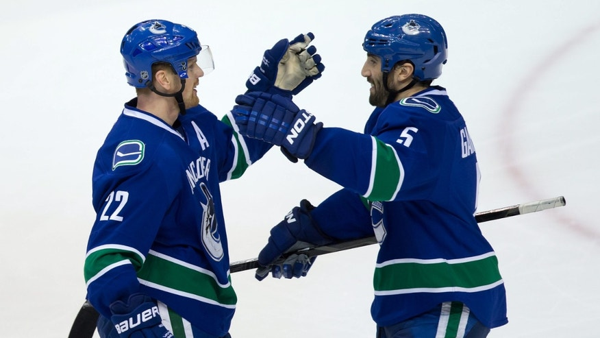 Vancouver Canucks' Daniel Sedin, left, of Sweden, and Jason Garrison celebrate Sedin's goal against the Edmonton Oilers during second-period NHL hockey game action in Vancouver, British Columbia, Friday, Dec. 13, 2013. (AP Photo/The Canadian Press, Darryl Dyck)