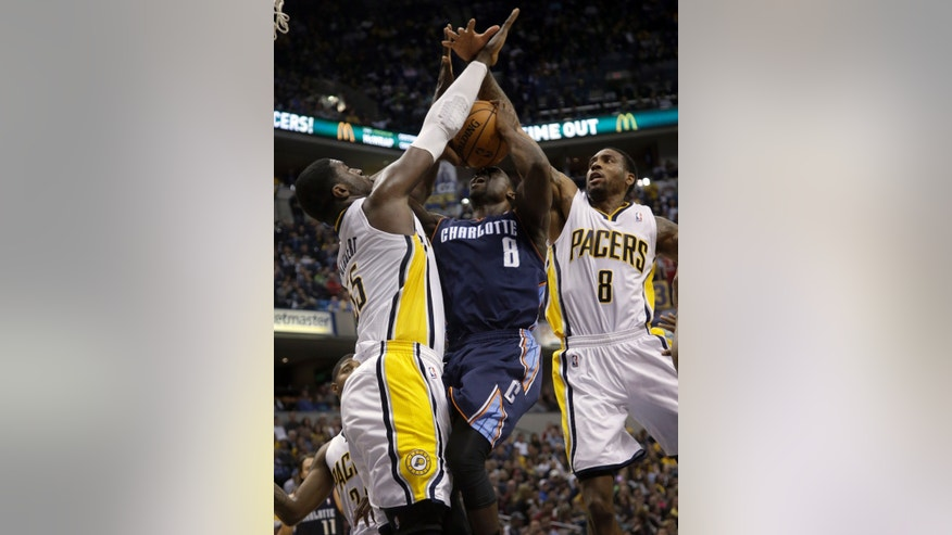 Indiana Pacers defenders, Rasual Butler, right, and Roy Hibbert, left, double-team Charlotte Bobcats guard Ben Gordon during the first half of an NBA basketball game in Indianapolis, Friday, Dec. 13, 2013. Gordon had the ball knocked away on the play. (AP Photo/AJ Mast)