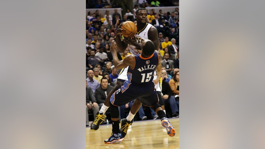Indiana Pacers guard Lance Stephenson, top, commits an offensive foul on Charlotte Bobcats guard Kemba Walker (15) during the second half of an NBA basketball game in Indianapolis, Friday, Dec. 13, 2013. The Pacers won 99-94. (AP Photo/AJ Mast)