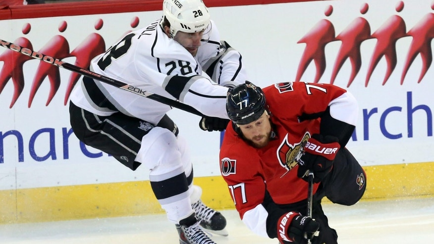 Ottawa Senators' Joe Corvo (77) is checked by Los Angles King' Jarett Stoll during the first period of an NHL hockey game in Ottawa, Saturday, Dec. 14, 2013. (AP Photo/The Canadian Press, Fred Chartrand)
