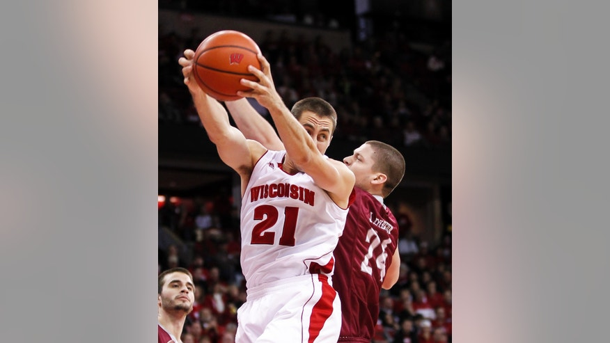 Wisconsin's Josh Gasser (21) pulls a defensive rebound away from Eastern Kentucky's Jeff Johnson during the first half of an NCAA college basketball game Saturday, Dec. 14, 2013, in Madison, Wis. (AP Photo/Andy Manis)