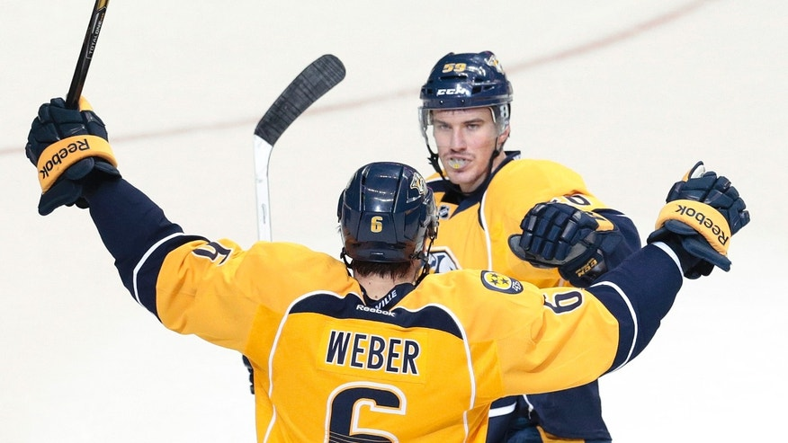Nashville Predators defenseman Roman Josi, top, of Switzerland, celebrates with teammate Shea Weber (6) after scoring against the San Jose Sharks in the second period of an NHL hockey game on Saturday, Dec. 14, 2013, in Nashville, Tenn. (AP Photo/Mark Humphrey)