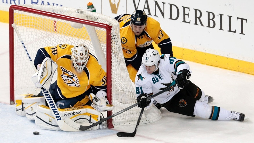 San Jose Sharks center Tyler Kennedy (81) shoots against Nashville Predators goalie Carter Hutton (30) in the second period of an NHL hockey game on Saturday, Dec. 14, 2013, in Nashville, Tenn. Predators forward Nick Spaling (13) also defends on the play. (AP Photo/Mark Humphrey)