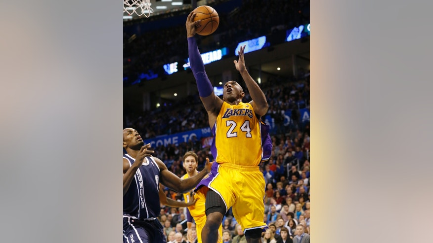 Los Angeles Lakers Kobe Bryant (24) shoots in front of Oklahoma City Thunder forward Serge Ibaka (9) in the second quarter of an NBA basketball game in Oklahoma City, Friday, Dec. 13, 2013. (AP Photo/Sue Ogrocki)