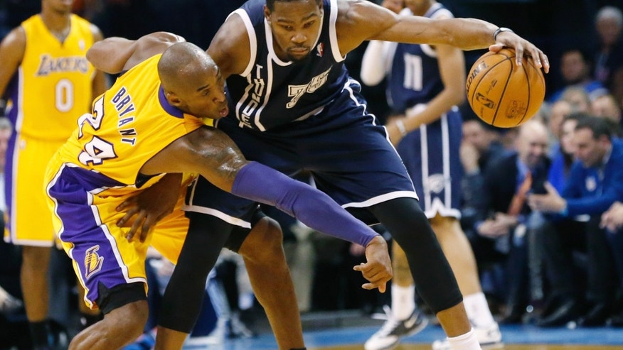 Oklahoma City Thunder forward Kevin Durant (35) keeps the ball away from Los Angeles Lakers Kobe Bryant (24) in the second quarter of an NBA basketball game in Oklahoma City, Friday, Dec. 13, 2013. (AP Photo/Sue Ogrocki)